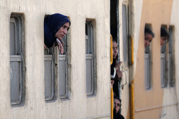 People look out of the windows of a train passing by the train which derailed in al-Badrasheen area of Giza province, south of Egypt's capital Cairo