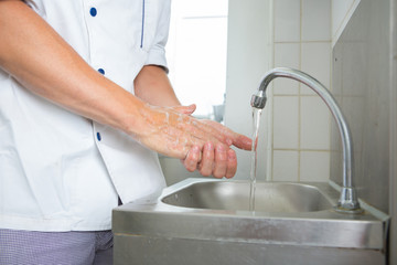 handsome chef washing his hands in commercial kitchen