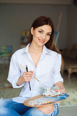 Portrait of talented young woman painting picture in art studio with inspiration