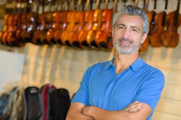 man posing in a violin store