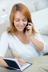 woman writing contact list from mobile phone into her agenda