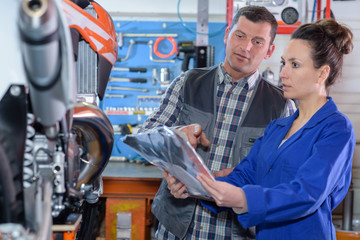 Mechanics examining motorcycle
