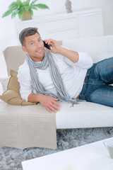 Man on couch on telephone, surprised expression