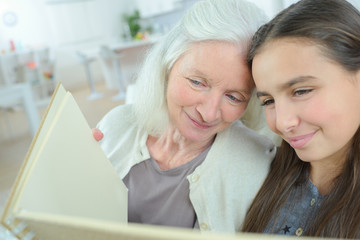 woman and her granddaughter looking at an album