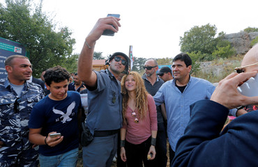 Colombian singer Shakira poses for a selfie with a police officer during her visit to Tannourine Cedars Reserve, in Tannourine