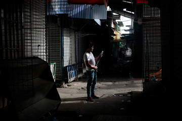 A man stands with a shotgun in front of stalls, closed during a national strike at the Oriental Market in Managua