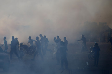 Palestinians react as tear gas was fired by Israeli troops during a protest at the Israel-Gaza border in the southern Gaza Strip