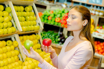 Lady holding apples of two different varieties