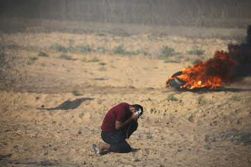 Palestinian reacts to tear gas fired by Israeli troops during a protest at the Israel-Gaza border in the southern Gaza Strip
