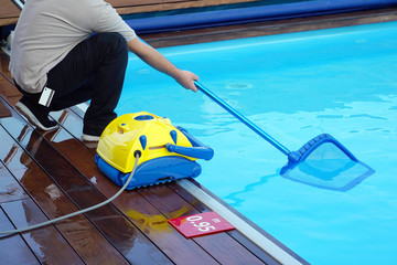 Pool cleaner during his work. Cleaning robot for cleaning the botton of swimming pools. Hotel staff worker cleaning the pool.