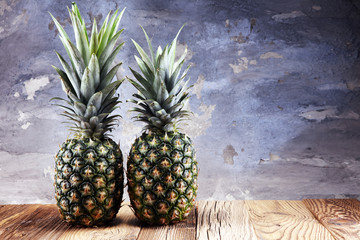 Ripe pineapples on rustic wooden table