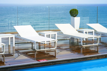 Loungers, standing on a wooden floor on the background of the sea. View from the pool to the terrace of the hotel suite rooms.
