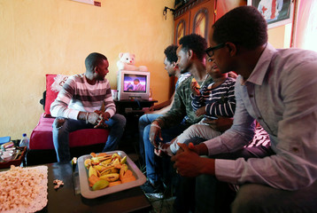 Eritrean refugees watch a news about Ethiopia and Eritrea peace deal in their apartment in Addis Ababa
