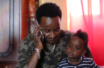 Henok Asgedom, an Eritrean refugee uses his mobile phone to talk to his mother in Eritrea as he holds his son Nebiyu Henok in his apartment in Addis Ababa