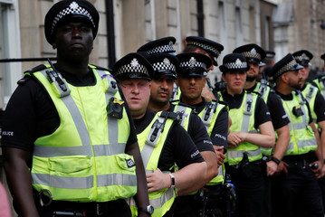 Police officers stand in reserve during a protest against the visit of U.S. President Donald Trump, in central London