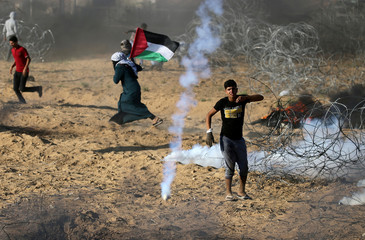 Palestinians react to tear gas fired by Israeli troops during a protest at the Israel-Gaza border in the southern Gaza Strip