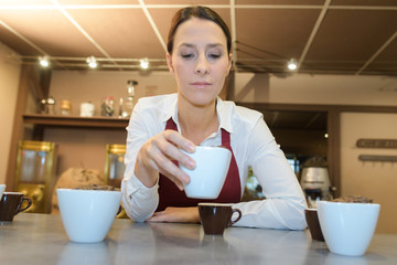 friendly female barista holding cup of cappuccino in coffee shop