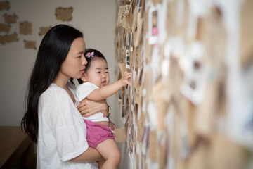 A baby looking at the picture on the wall in its mother's arms