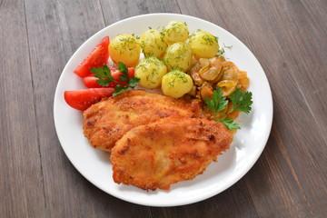 filety z kurczaka z ziemniakami surówką i pomidorem