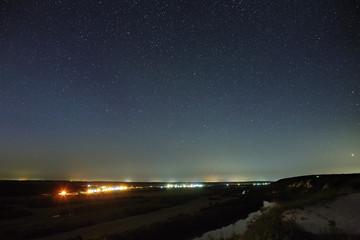 Stars in the night sky over the river valley and city. The cosmic space is photographed on a long exposure.