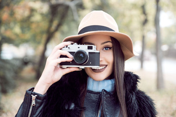 Young woman taking photos with vintage camera outdoors