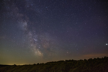 The stars of the Milky Way in the night sky over a hilly landscape. The cosmic space is photographed on a long exposure.