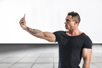 Handsome muscular young man taking selfie with cell phone while striking bodybuilding pose, isolated
