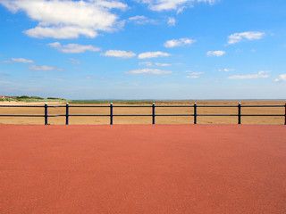 scenic view form the end of the promenade at saint annes on the sea in lancashire with railings in front of the sandy beach with grass covered dunes and the ribble estuary in the distance in summer