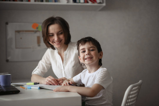 beautiful mother teaches her son at home at table