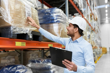wholesale, logistic, business, export and people concept - man or manager in helmet with clipboard checking goods at warehouse