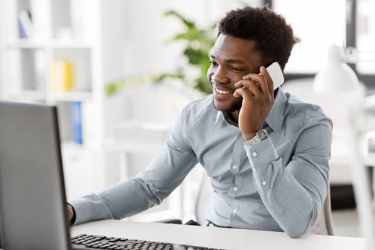 business, people, communication and technology concept - smiling african american businessman with computer calling on smartphone at office