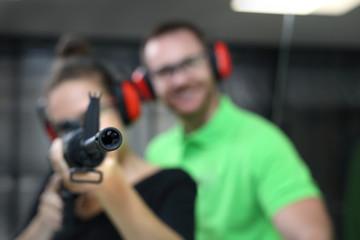 Strzelnica. Kobieta strzela z karabinu. Kobieta strzela z broni na strzelnicy pod okiem instruktora.