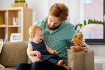 family, fatherhood and people concept - happy red haired father and little baby daughter playing with teddy bear at home