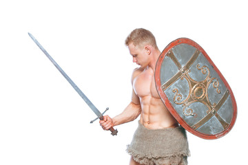 Bodybuilder man posing with a sword and shield isolated on white background. Serious shirtless man demonstrating his mascular body.