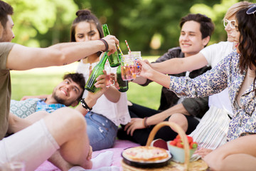 leisure, people and celebration concept - happy friends clinking non alcoholic drinks at picnic in summer park