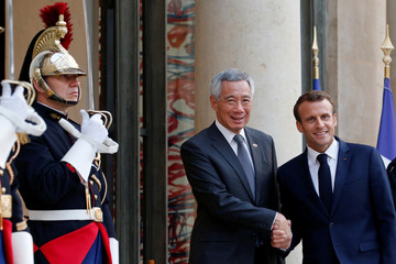 French President Emmanuel Macron welcomes Singapore's Prime Minister Lee Hsien Loong as he arrives at the Elysee Palace in Paris