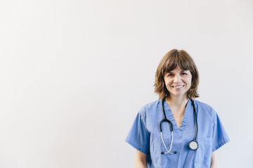 Portrait of smiling female doctor with stethoscope standing against white background