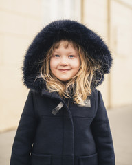 Portrait of smiling girl wearing fur coat while standing outdoors