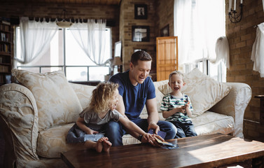 Happy father playing with children while sitting on sofa in living room