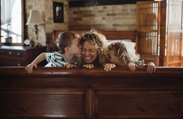 Happy children kissing mother on bed at home