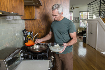 Senior man pouring batter in frying pan while cooking at home