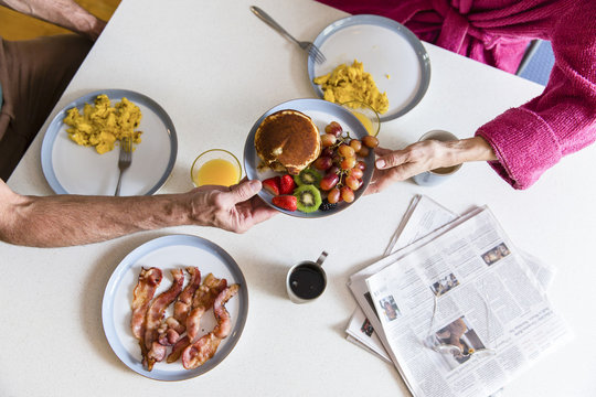 Midsection of couple holding plate with food over dining table at home
