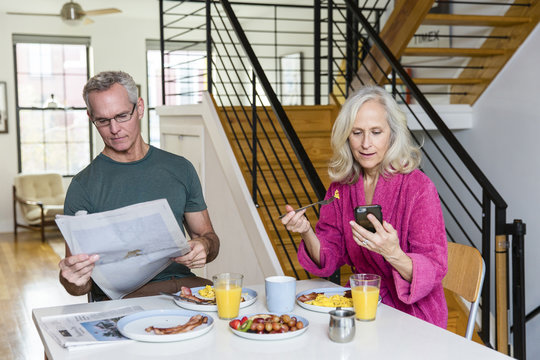 Man reading newspaper while woman using smart phone at dining table