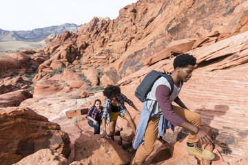 Friends hiking on rock formations during sunny day