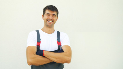 Portrait happy caucasian male industrial worker in work clothes crossing hands looking at camera isolated on light background with free space and copy space. Construction, architect, emotion concept