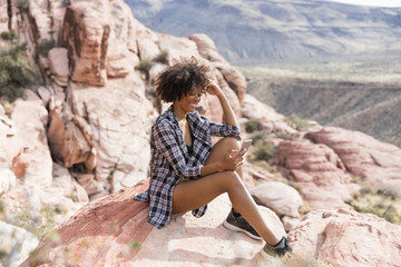 Woman using smart phone while sitting on rock formation