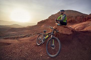 Full length of hiker by mountain bike sitting on rocks at desert during sunset