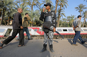 A police officer stands guard next to a passenger train which derailed in al-Badrasheen area of Giza province, south of Egypt's capital Cairo