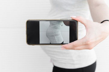 Pregnant woman taking picture of belly