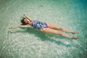 Beautiful woman lying on water surface in crystal clear sea
